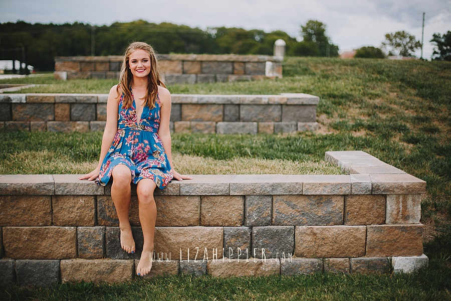 blonde high school senior in blue flowered dress sits on stone wall