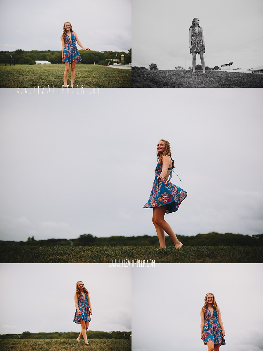 senior girl in blue dress dances on grass for photo shoot