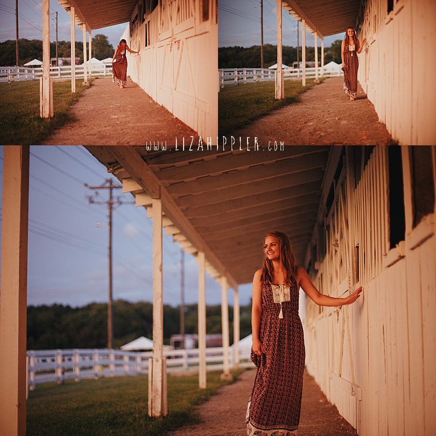 senior girl walks along white horse stables in plantation maxi dress looking at the sunset