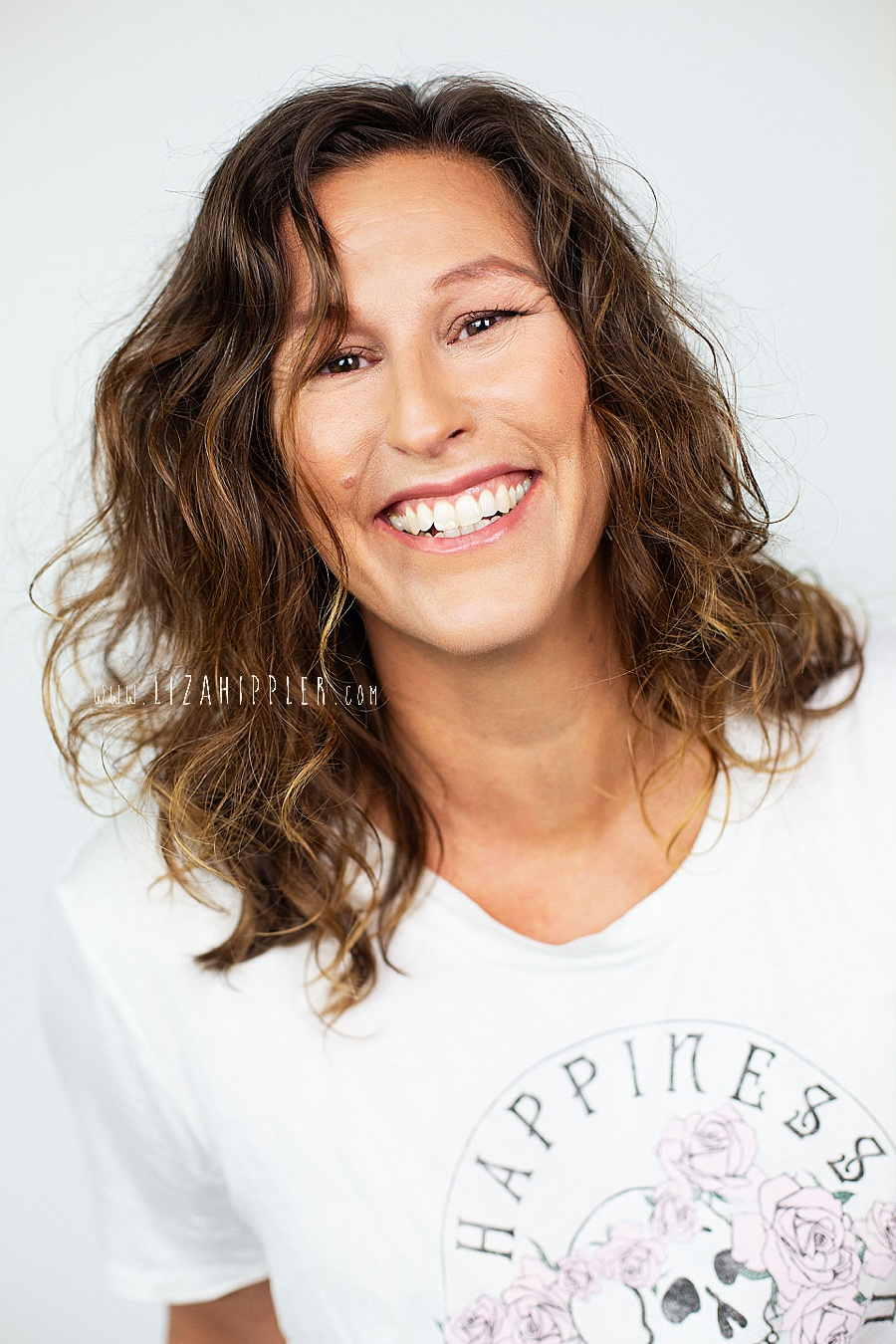 happy woman with wavy hair in white t-shirt with skull