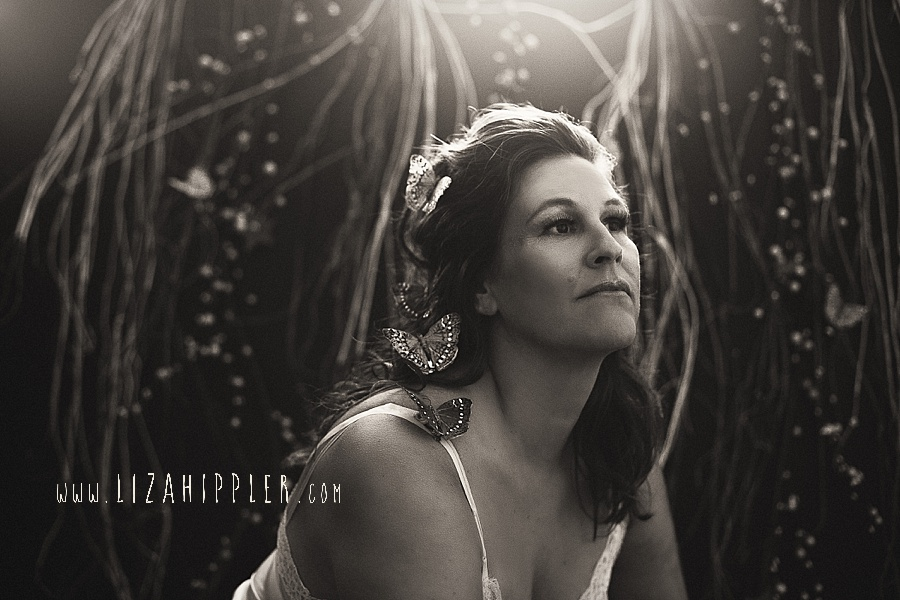 black and white portrait of woman with butterflies in her hair looks off