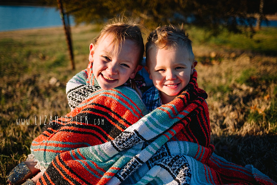 young blonde brother and sister snuggle under mexican blanket