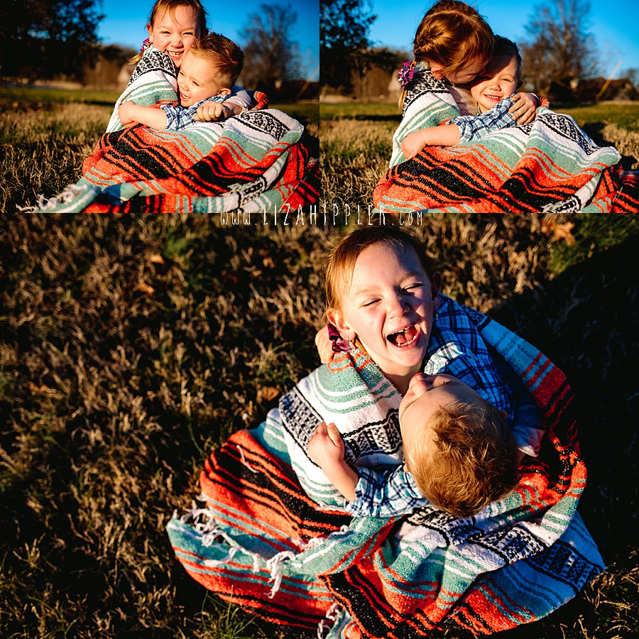 young brother and sister being goofballs with blanket in the grass