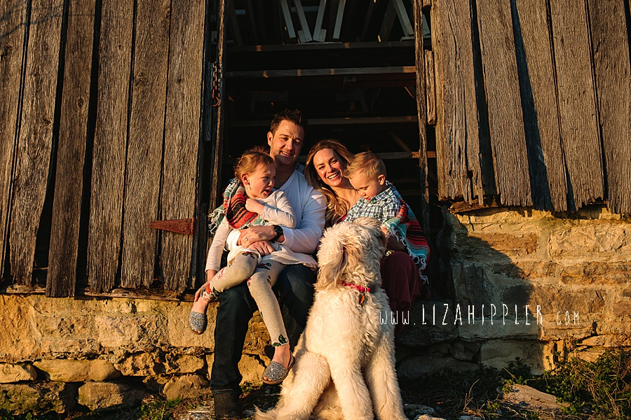 family snuggles in opening of barn in golden hour light