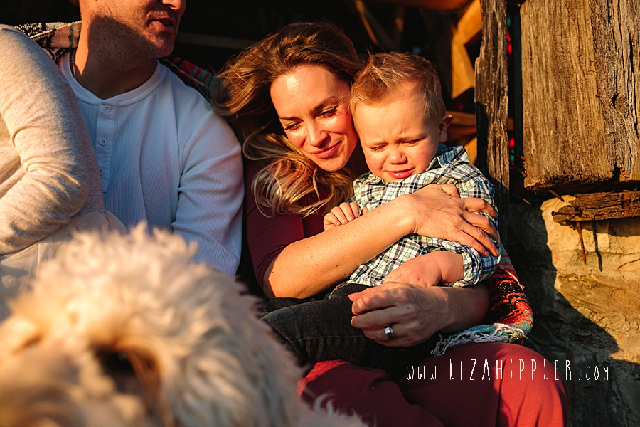 mom snuggles toddler son in golden hour light