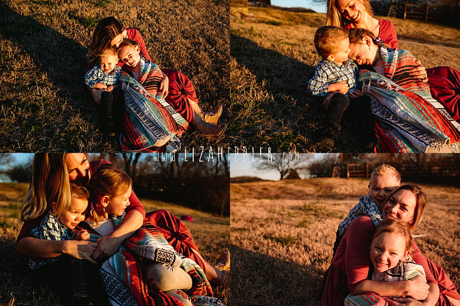 blonde mom and her two young children snuggle under a blanket in a field
