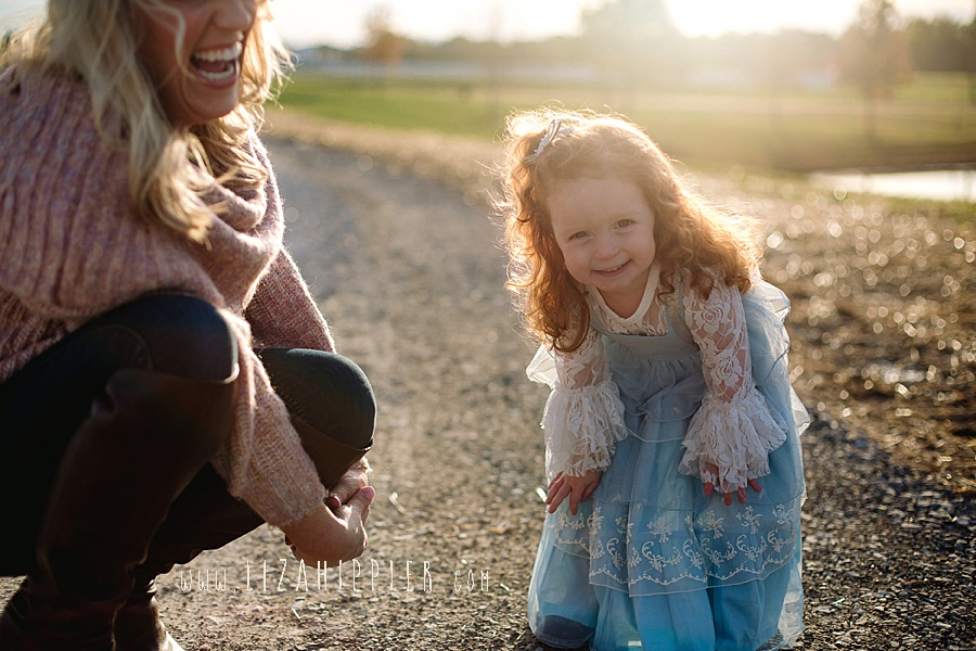mom and toddler daughter laugh during golden hour