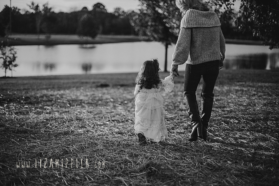 black and white image of mom holding young daughters hand and walking away