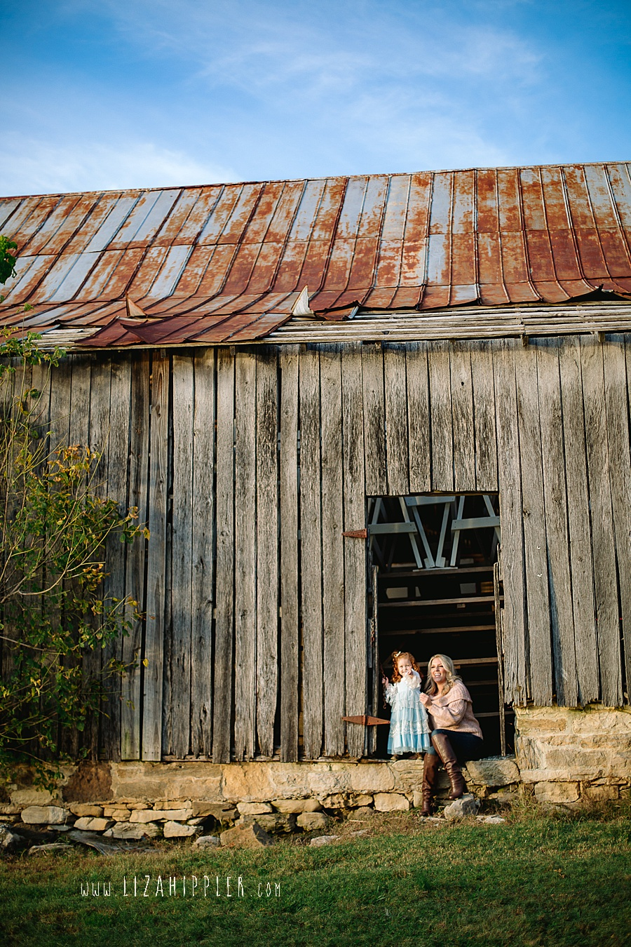 mommy and redhead toddler daughter sit by a barn
