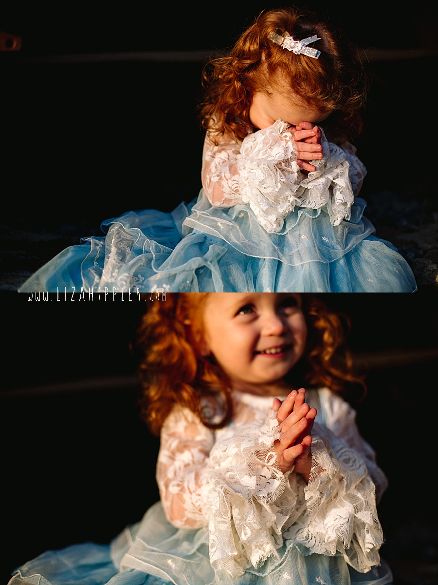redheaded toddler in blue fluffy dress says a prayer