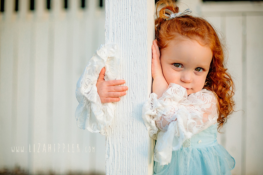adorable little girl poses for camera and leans against white post