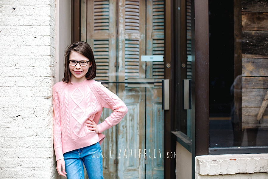 brunette girl in pink sweater and glasses