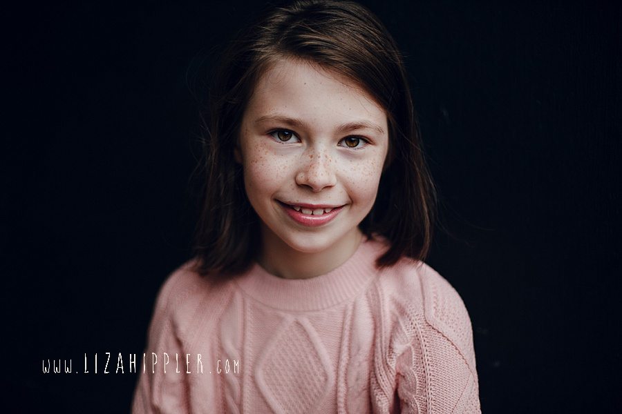 beautiful portrait of 8 year old girl in pink sweater
