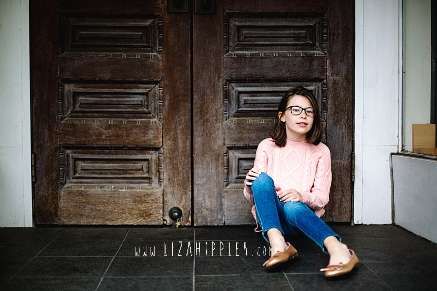 adorable girl in glasses, jeans and pink sweater sits in front of double doors