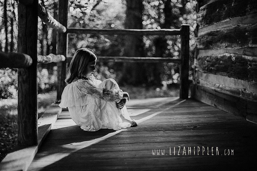 black and white photo of young girl on log cabin porch