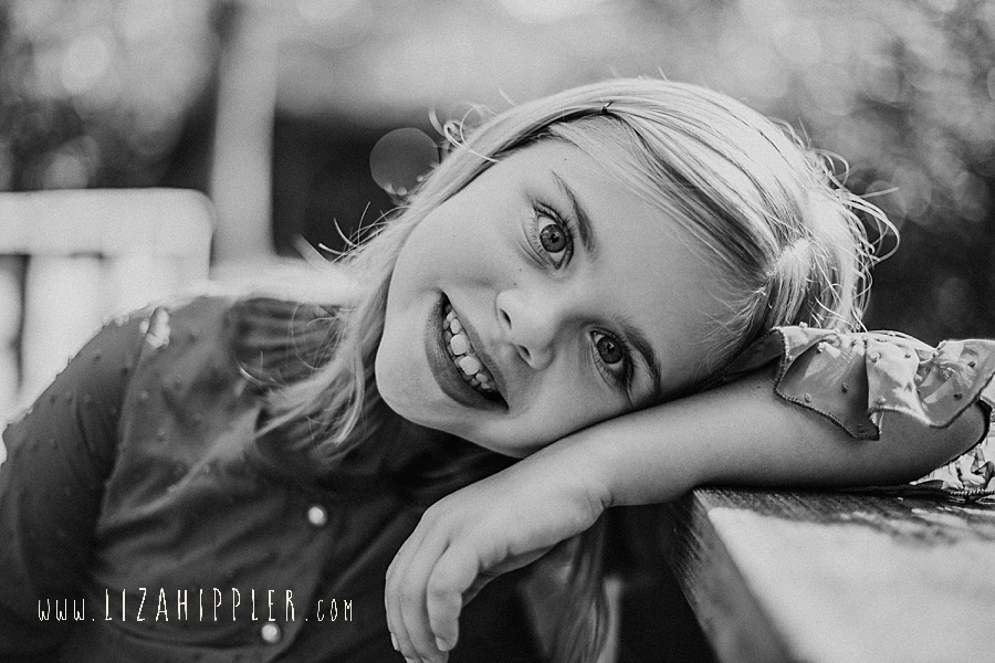 cute little girl leans on her arm and smiles