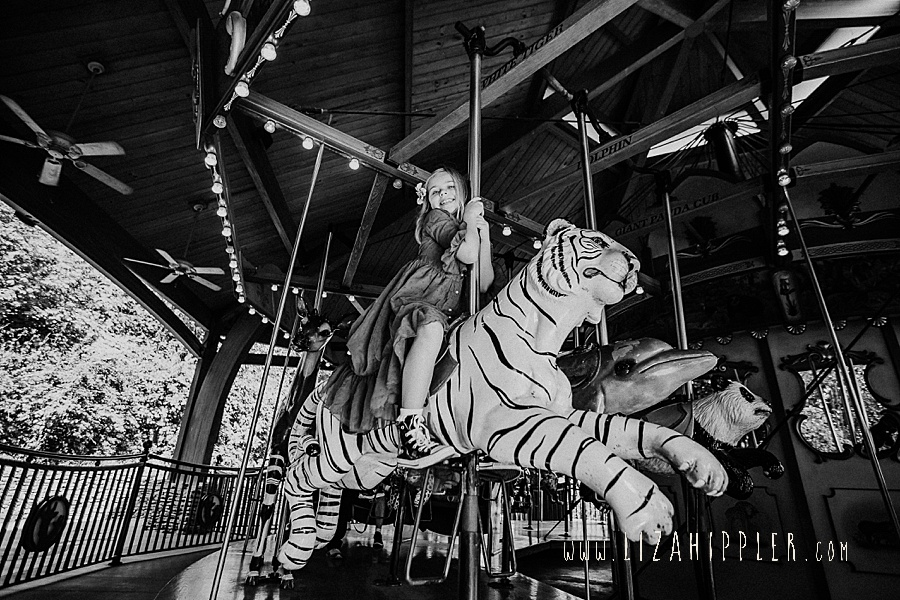 black and white photo of girl riding carousel