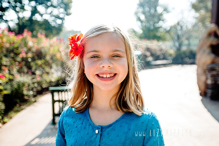 blonde third grader with blue dress and orange flower in her hair