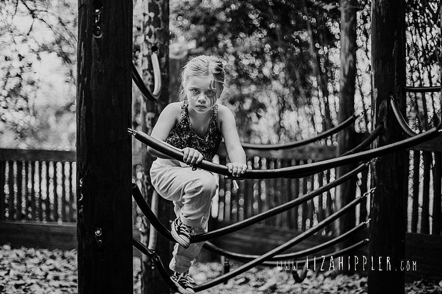 young girl with facepaint climbs on jungle gym at nashville zoo grassmere