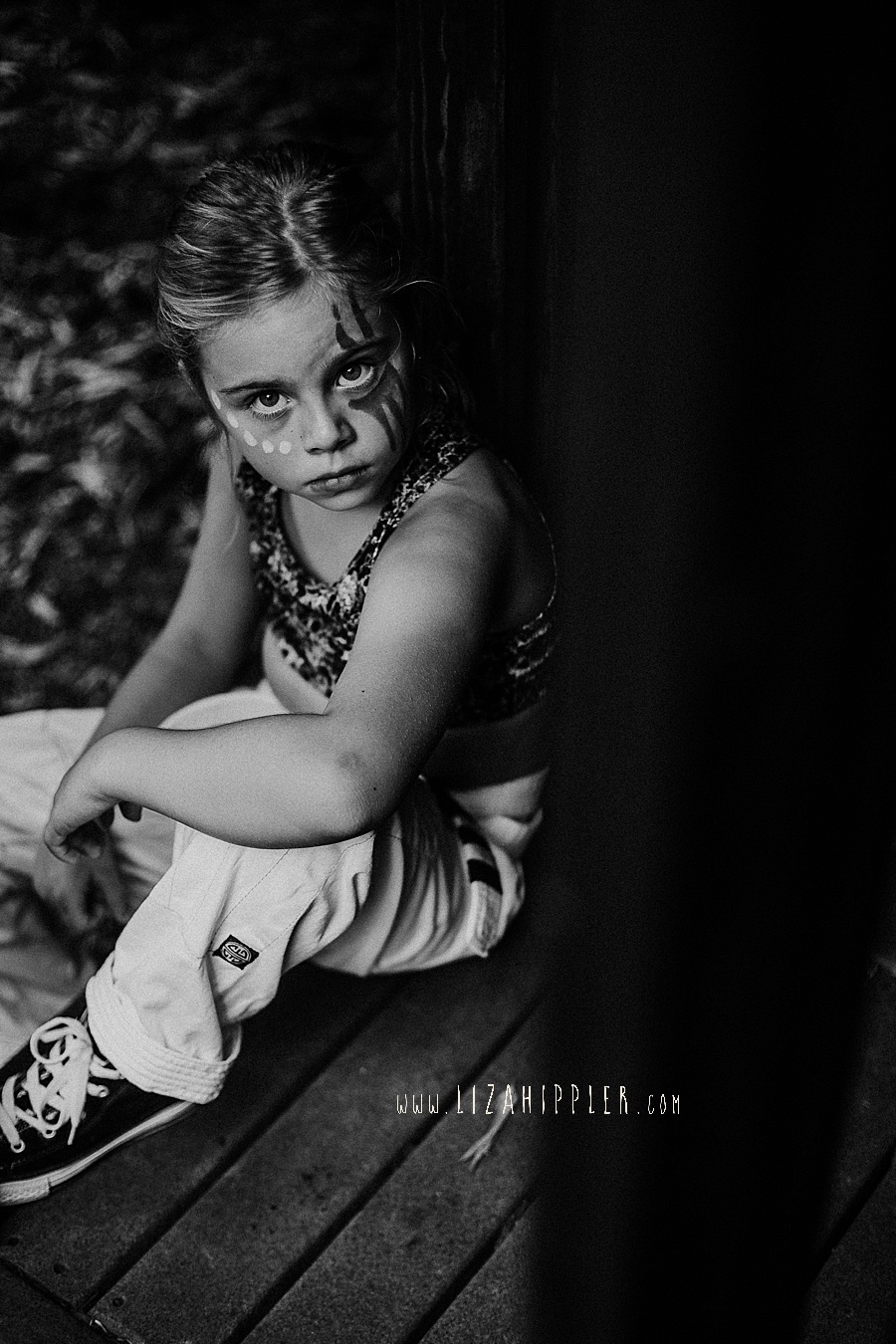 black and white photo of young girl with facepaint looking tough