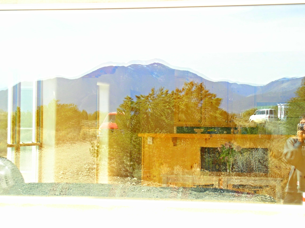 Taos mountains reflected in picture window.