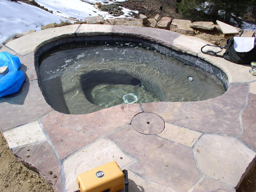 A cast concrete hot tub with flagstone edging sits at the edge of the patio.