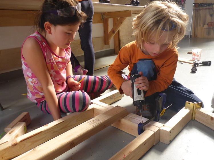 Una niña y un niño taladrando madera en Tinkering School, San Francisco (Estados Unidos)