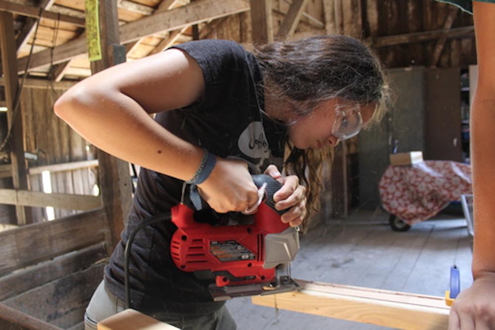 Una joven cortando madera con una caladora, Tinkering School, San Francisco (EEUU)