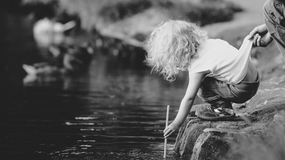La seguridad ante todo: una mano adulta sujeta a un niño que juega al borde del río.Safety First, por Lukas Kr., CC BY-NC 2.0.