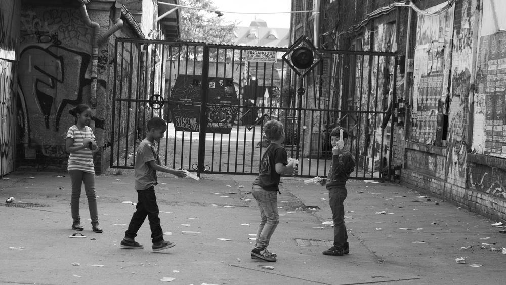 """Niñas y niños jugando a ser pistoleros. Foto: """"Gunmen at Suicide Circus"""", por Sascha Kohlmann, CC BY-SA 2.0"""