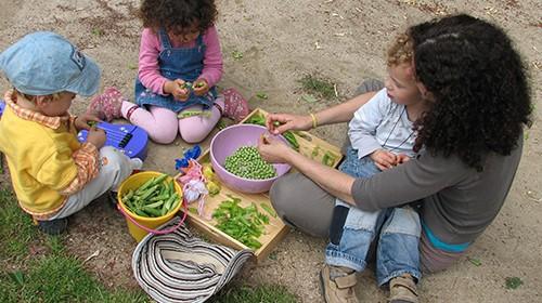 Niños y una acompañante pelando guisantes para la comida.
