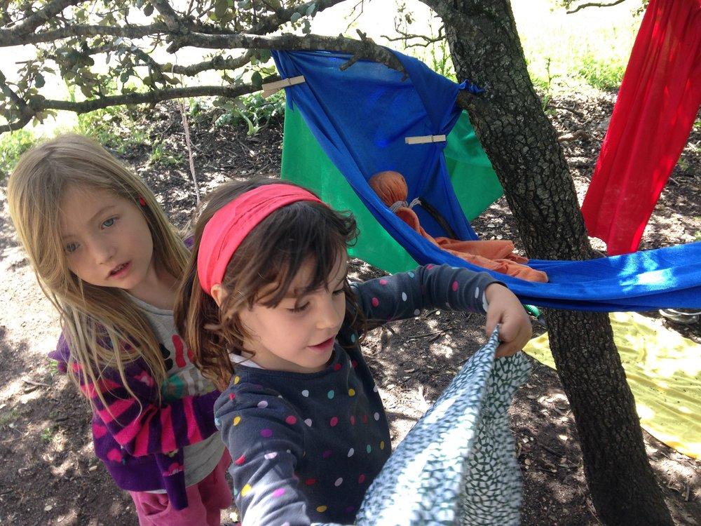 Dos niñas jugando a las casitas con telas de colores.