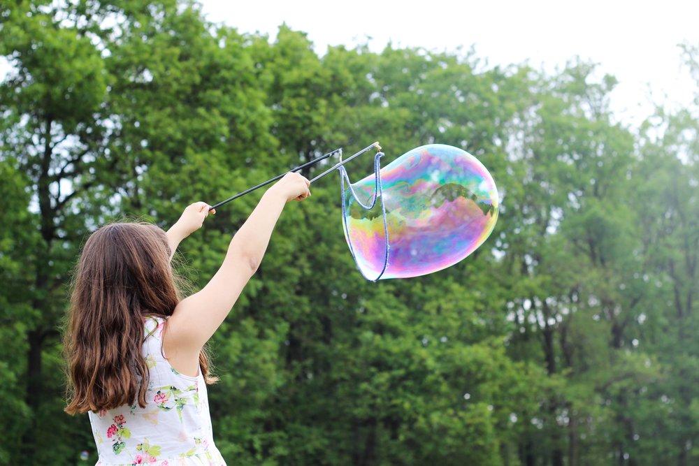 Una niña disfruta haciendo pompas de jabón.
