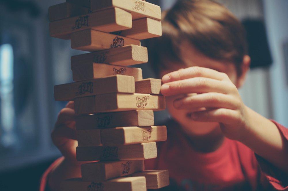 Un niño construye una torre con bloques de madera.