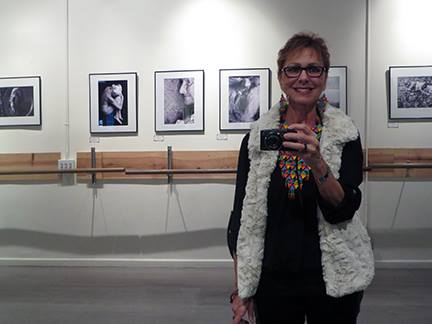 "Mara Zaslove in front of her photography series, ""Ageless Beauty"""