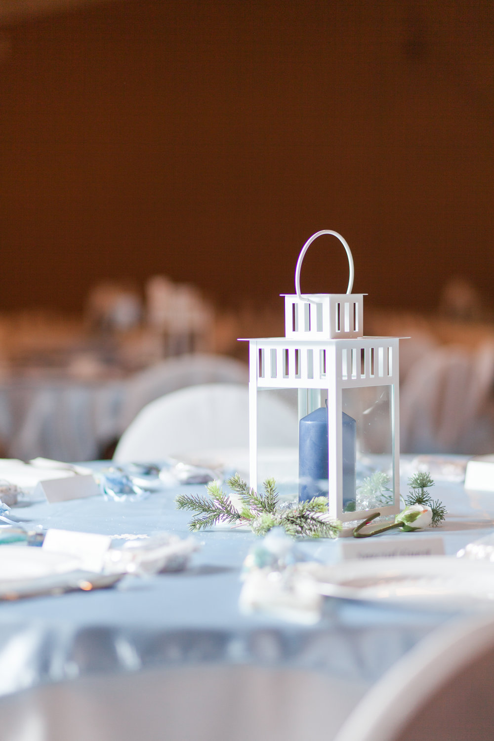 winter lantern wedding decoration with pine and glitter table setting, centerpiece