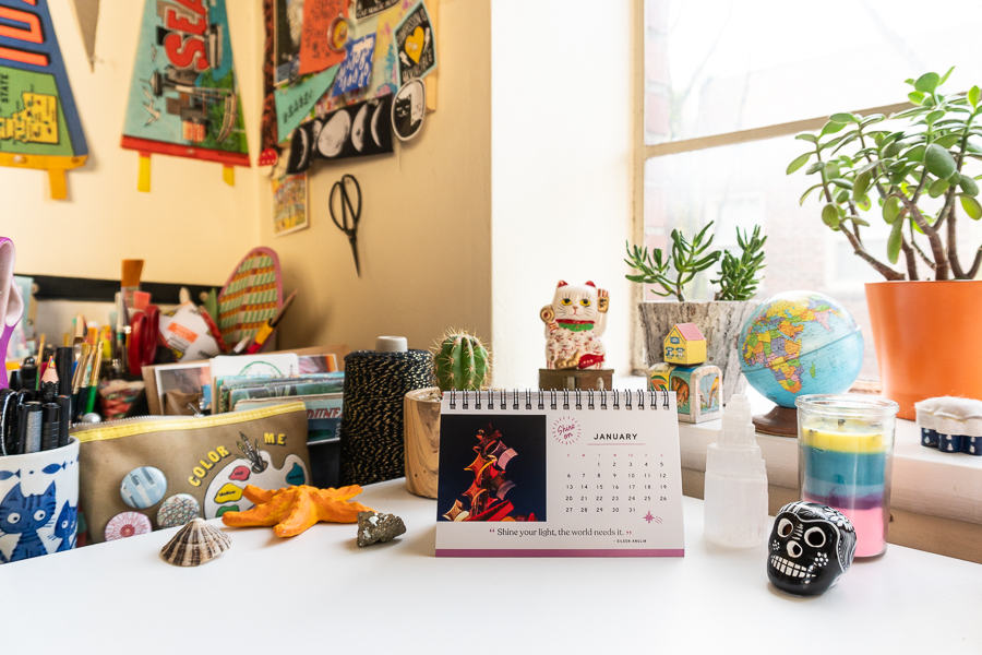 Desk with calendar and colorful trinkets. Creative studio space.