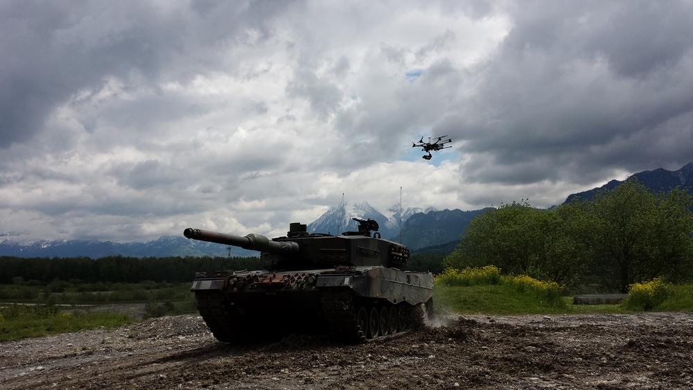 Leopard tank followed by a drone