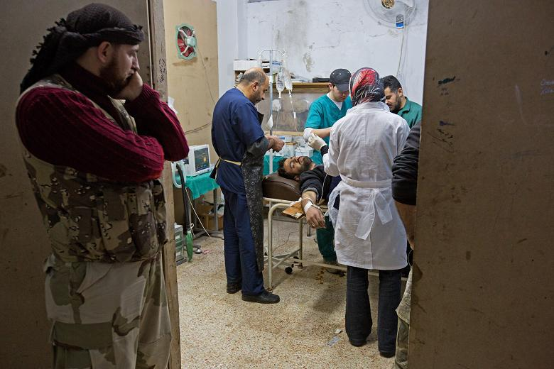 A rebel fighter looks on as a medical team works on a fallen comrade   Times photographer, Jack Hill