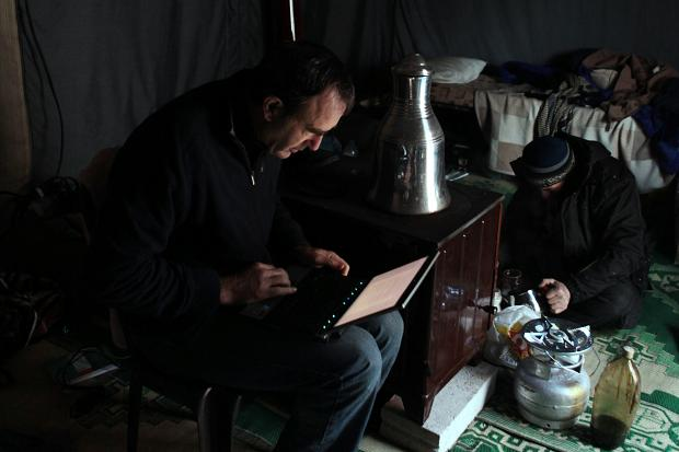 Martin Fletcher writes an article in a tent in Syria  Times photographer, Tom Pilston