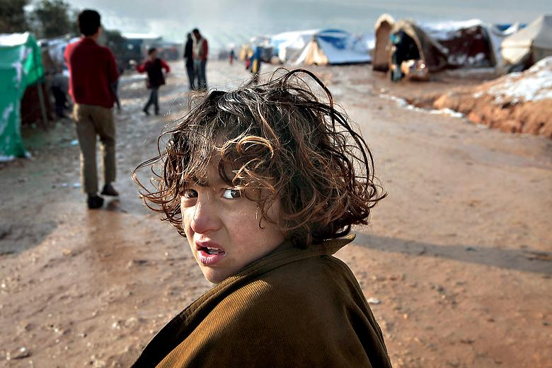 A bewildered child in Atmeh refugee camp after snow    Times photographer, Tom Pilston