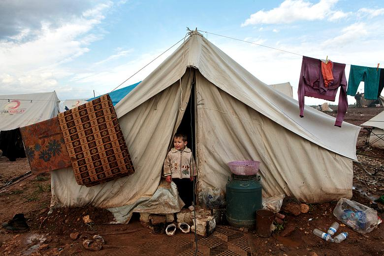 A youngster stands in front of his family's flimsy tent  Times photographer, Tom Pilston