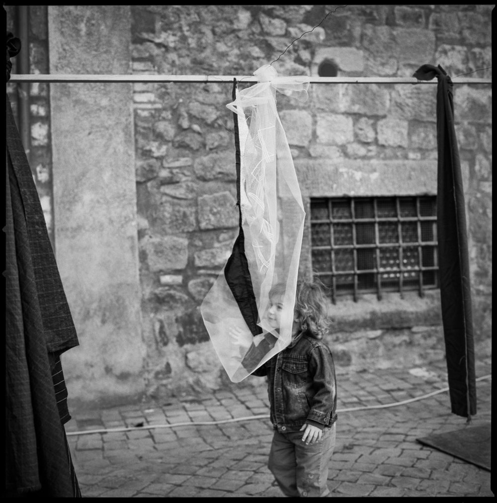Boy looking through fabric Viterbo, Italy 2011   Made with Hasselblad 501c with Kodak Tri-X 400 b&w film