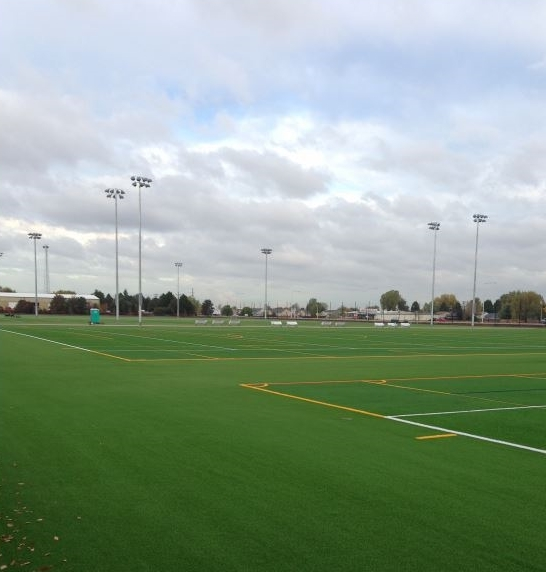 AURORA SPORTS PARK -  The expansion project consisted of furnishing and installing four (4) multi-sport synthetic turf fields, concrete seat wall surrounding fields, a low site wall with perimeter 30' tall safety fencing, concessions area, fully plumbed and heated restroom building, field identification on a scaffolding structure, 372 parking spaces, field lighting, parking, lot lighting, pedestrian walkways, natural turf practice area and landscaping.