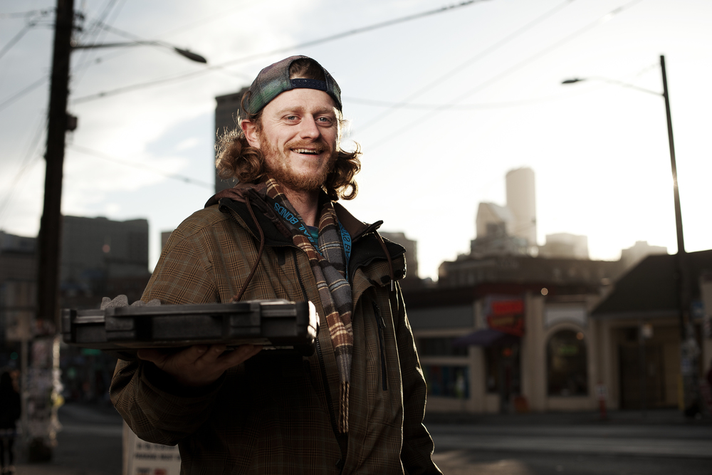 """Morgan walks around Seattle with this case, selling jewelry he makes out of various exotic rocks. I asked if I could take his photo, and he said, """"Sure. The satellites take them anyway."""""""