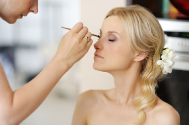 40757336 - young beautiful bride applying wedding make-up  by professional make-up artist