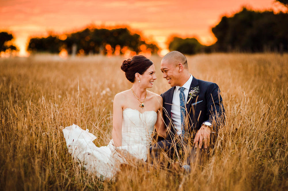 Dashing wedding couple sitting in field at sunset at Bracu in Bombay.jpg