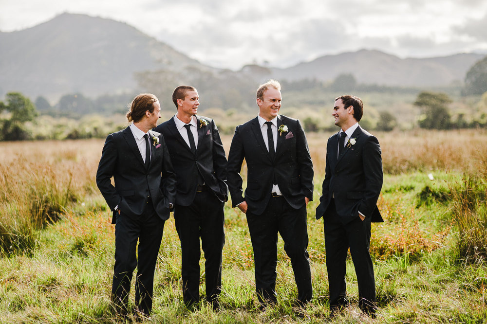 Groomsmen laughing in field.jpg