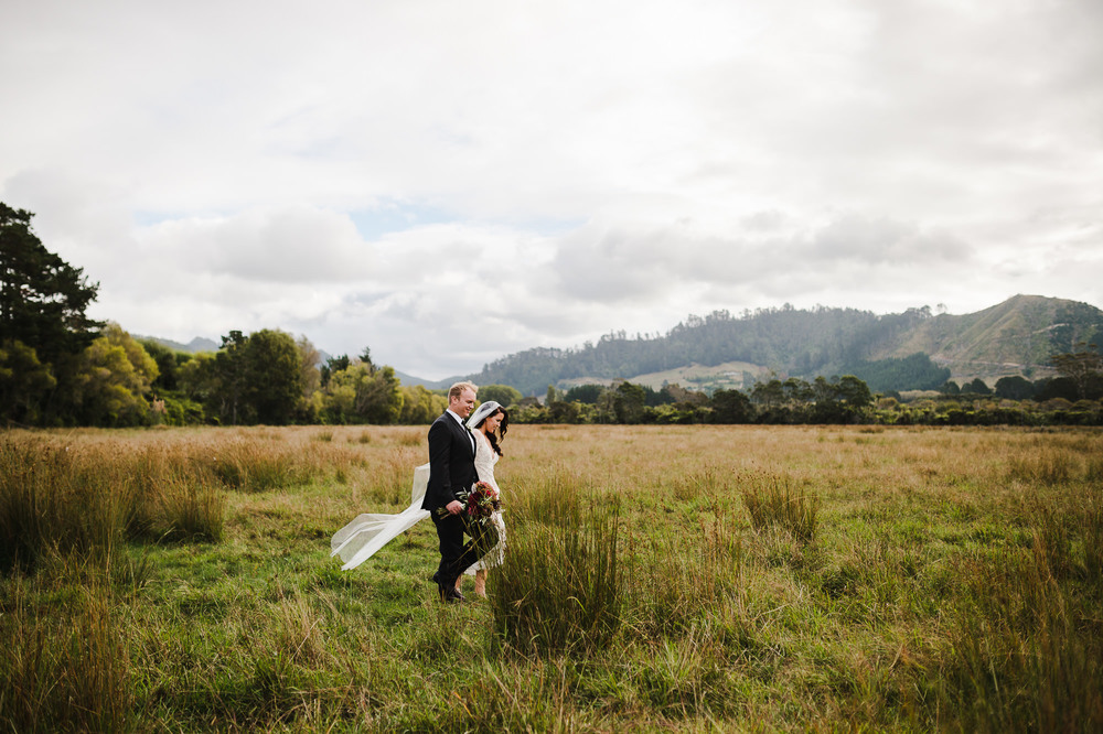 wedding couple walking through field in New Zealand.jpg