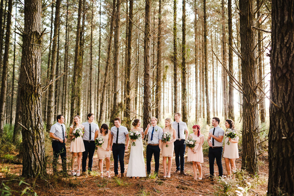 large bridal party laughing in auckland forest.jpg